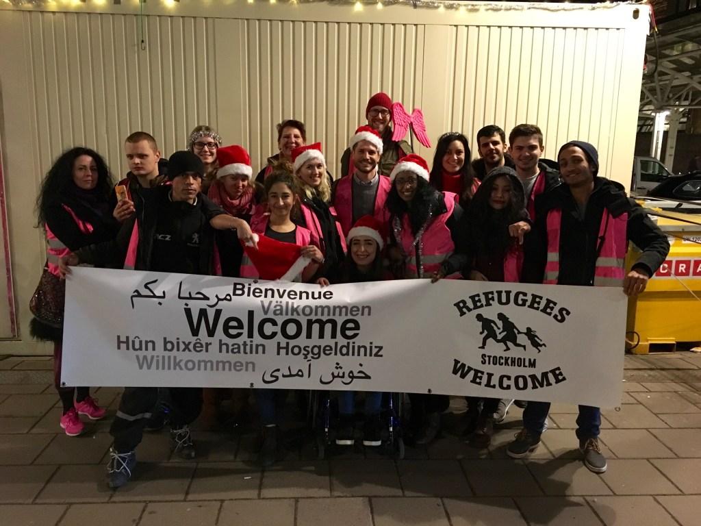 Refugees Welcome Stockholm - gruppbild utanför Centralstationen med rosa västar och tomtemössor för att önska god jul