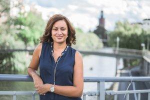 Maryem Nasri, projektledare på en bro över Klara sjö med Stockholms stadshus i bakgrunden. Fotograf: Caroline Frankesjö www.carolinefrankesjo.se