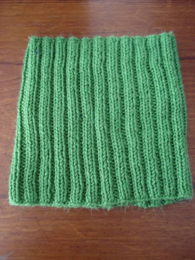 Knitted neck warmer in green yarn by Mary Warner, 2014.
