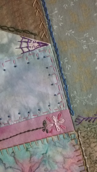 Spider web and flower on crazy quilt by Mary Warner, April 3, 2017.