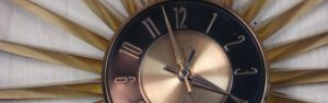 Closeup of metal bronze and black starburst wall clock, 2018.