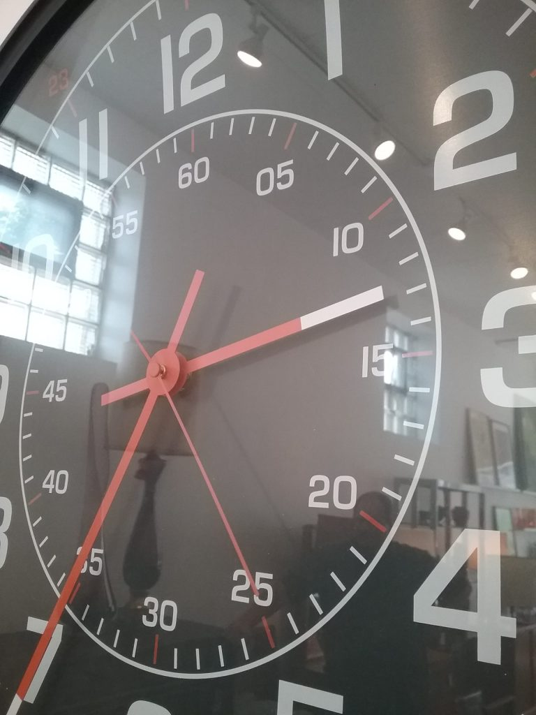 Black clock with white numbers and red and white hands, 2018.