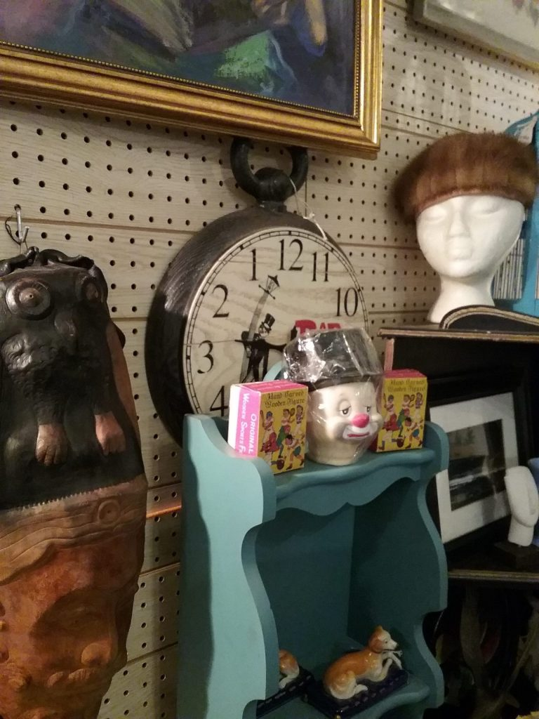 Clock peeking from behind other items at an antique shop in Ellicott City, Maryland, 2019. I had the impression upon seeing this that it could be a Natty Boh clock. Natty Boh is the nickname for National Bohemian Beer, which was originally brewed in Baltimore. The beer's mascot, called Natty Boh, is a one-eyed guy with a handlebar mustache and he can be seen in bars and restaurants all over Baltimore. I'm not sure I'm correct about whether this is a Natty Boh clock because the guy doesn't look quite the same.