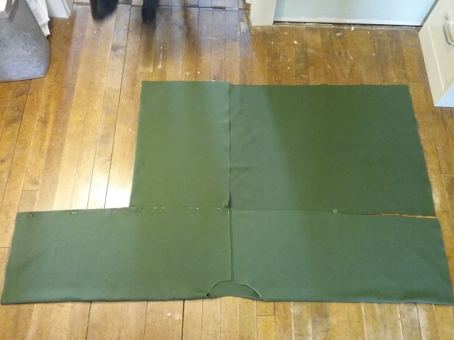 Dark green bog coat after making cuts, folding down sleeves, and folding over one bottom side. By Mary Warner, May 2019.