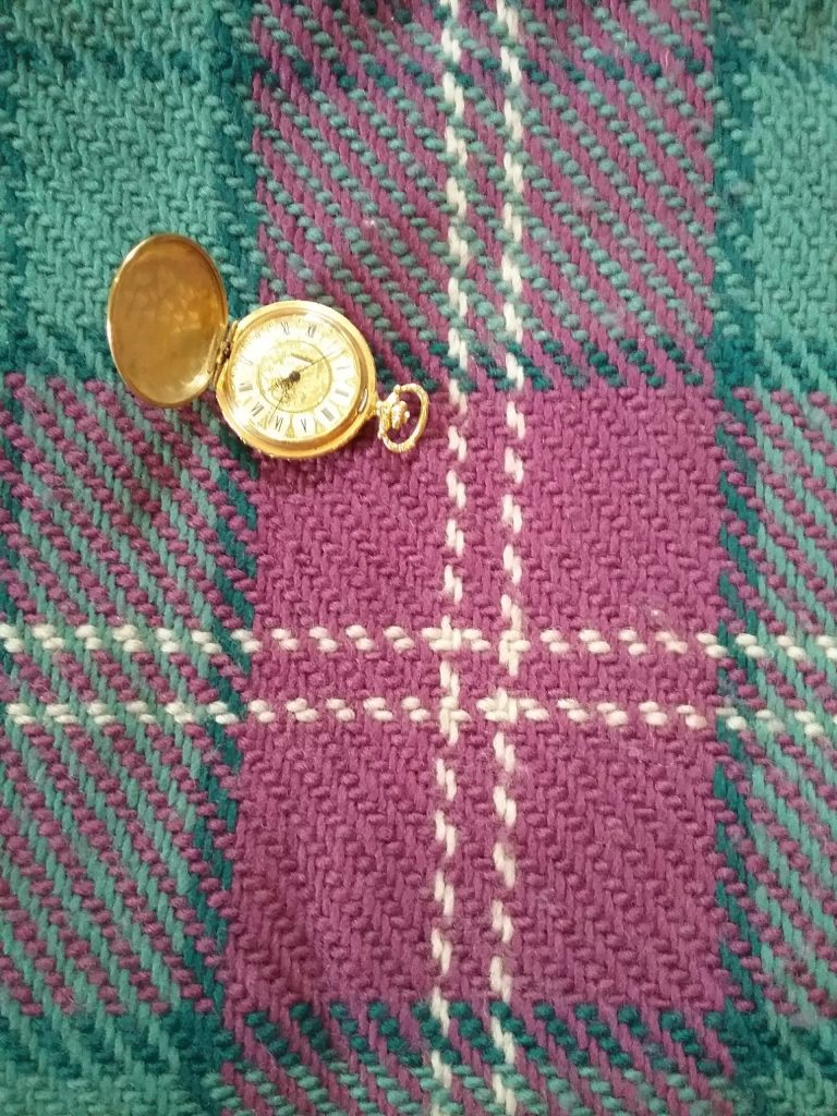 Tartan scarf woven by Mary Warner with pocket watch from Beatrice Rasmussen, 2019 photo.
