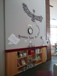Wall clock at St. Cloud Public Library surrounded by words that form a bird, 2019.