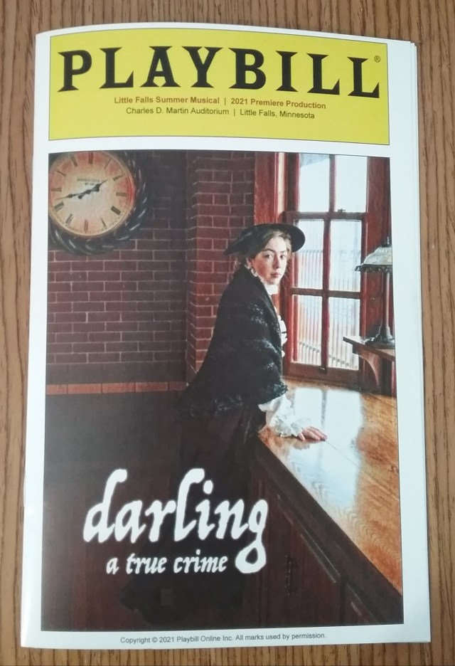 """Front of playbill for """"Darling,"""" written by Taryn Verley and performed by the Little Falls Summer Musical group, shows a young woman of the Victorian era leaning against a counter facing the windows in a train station, though the woman is looking at the viewer. August 2021."""