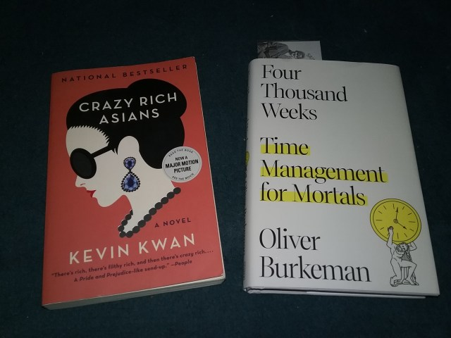 """The front covers of two books: """"Crazy Rich Asians"""" by Kevin Kwan (orange cover with the stylized profile of an Asian woman in sunglasses, earring, and pearl necklace on an orange background) and """"Four Thousand Weeks: Time Management for Mortals"""" by Oliver Burkeman (white cover with title in black, with Time Management for Mortals highlighted in yellow, small cartoon of a Greek or Roman man holding up a yellow clock in the lower right corner)."""