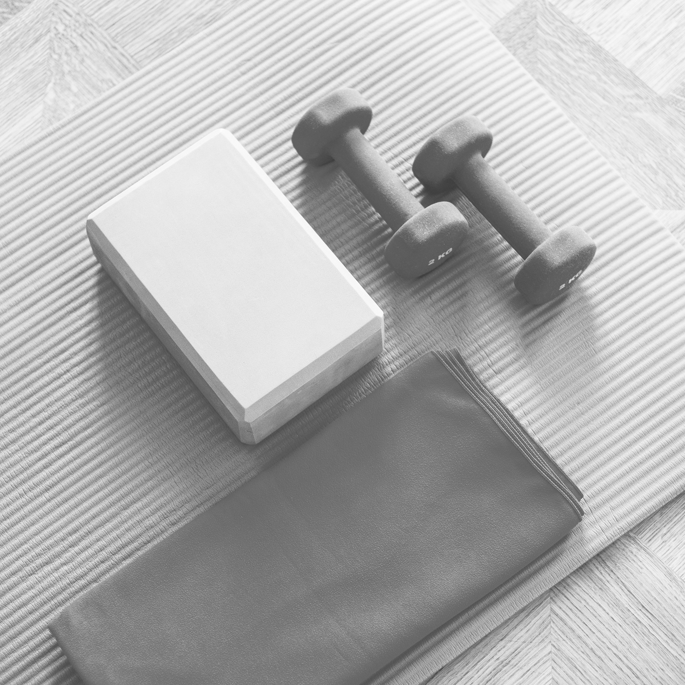Yoga mat, yoga block and weights to represent the idea of a gym