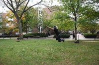 A Penn State student performs tricks on a slack line on the lawn in front of the Willard Building.