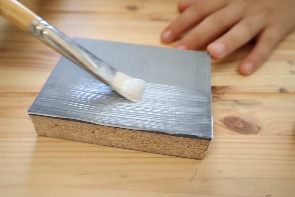 Apply Acrylic Medium to the linoleum with a brush