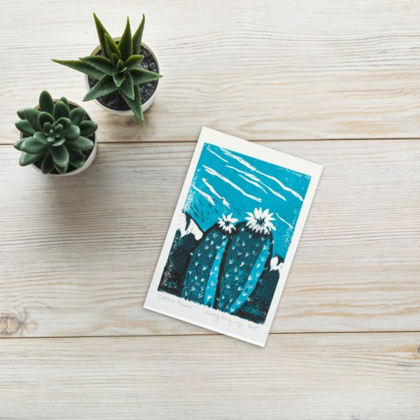 This is an image with a reproduction of two cactus flowers with a turquoise background printed on white paper.