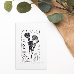 This is an image of a black chive flower printed on white paper.