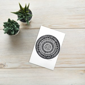 This is a print of a black mandala printed on white paper.