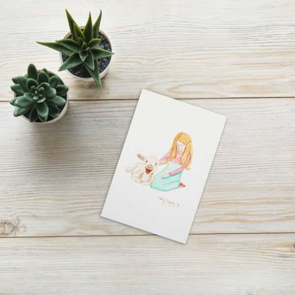 This is an image of a little blond girl illustration petting a lamb which is a reproduction of a painting printed on white paper.