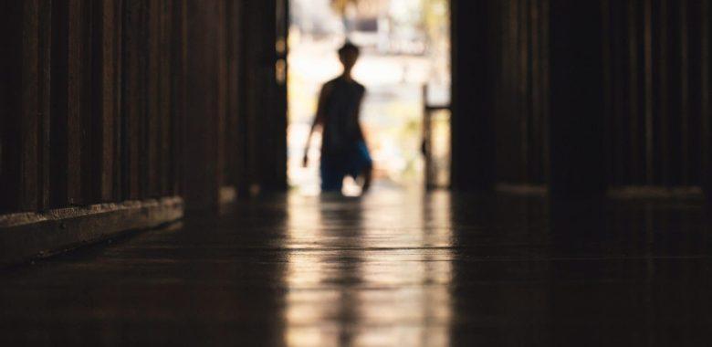 silhouette of boy going through a door
