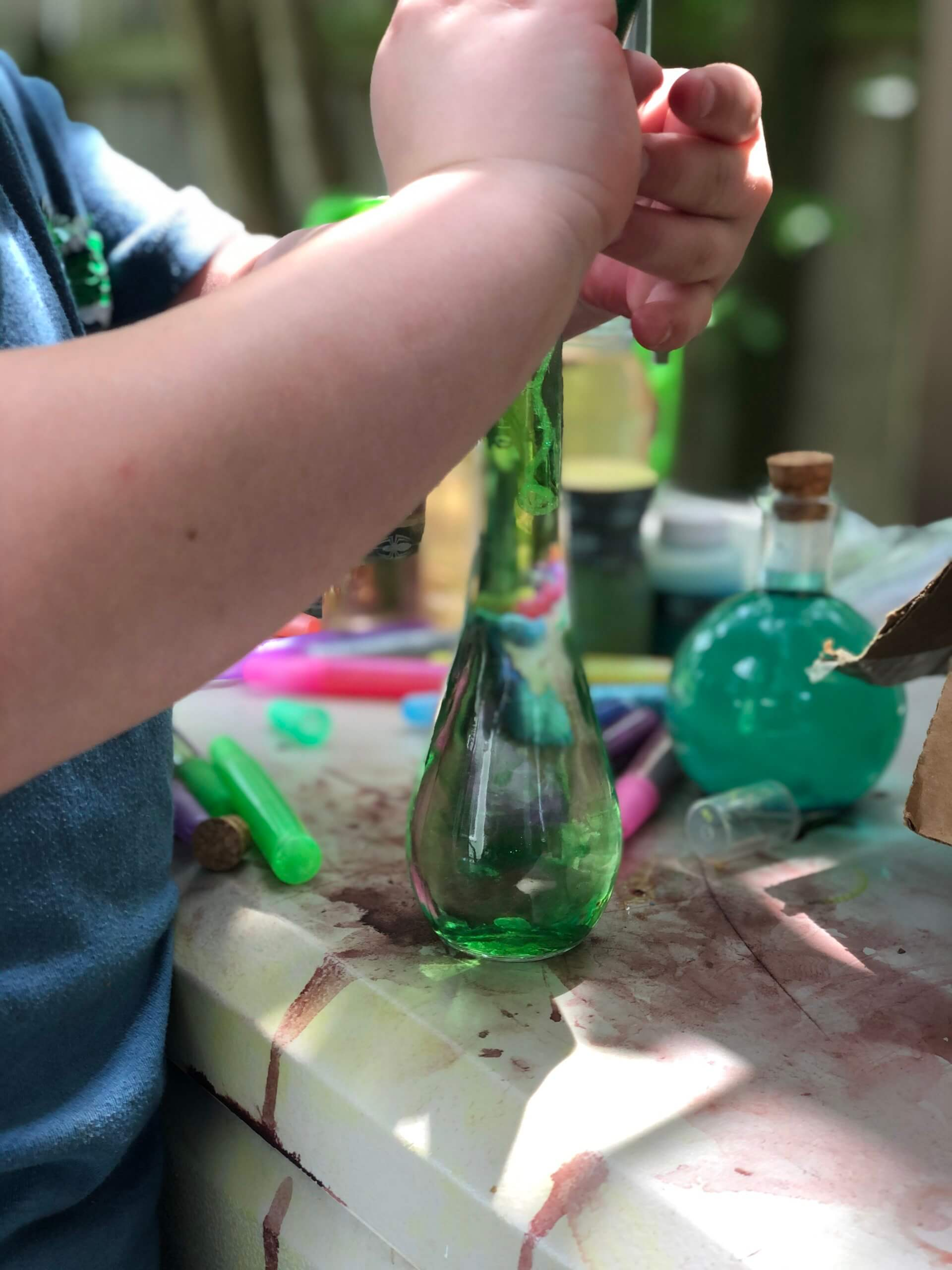 Child making magic potion with colorful bottles