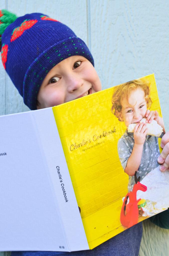 Child grinning behind cookbook