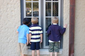 Curiosity: These three students are peering in the window of the lower school gym, trying to figure out what they'll be doing when they go to PE class later in the day.