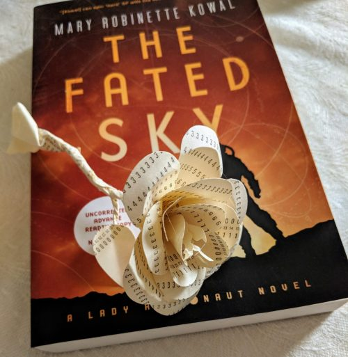 A papercraft flower made of punchcards atop The Fated Sky novel