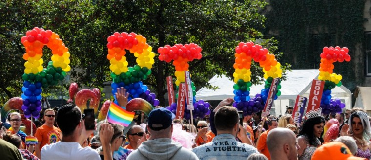 Picture of crowd at a Pride parade. Huge Balloons spelling out PRIDE in rainbow colors.