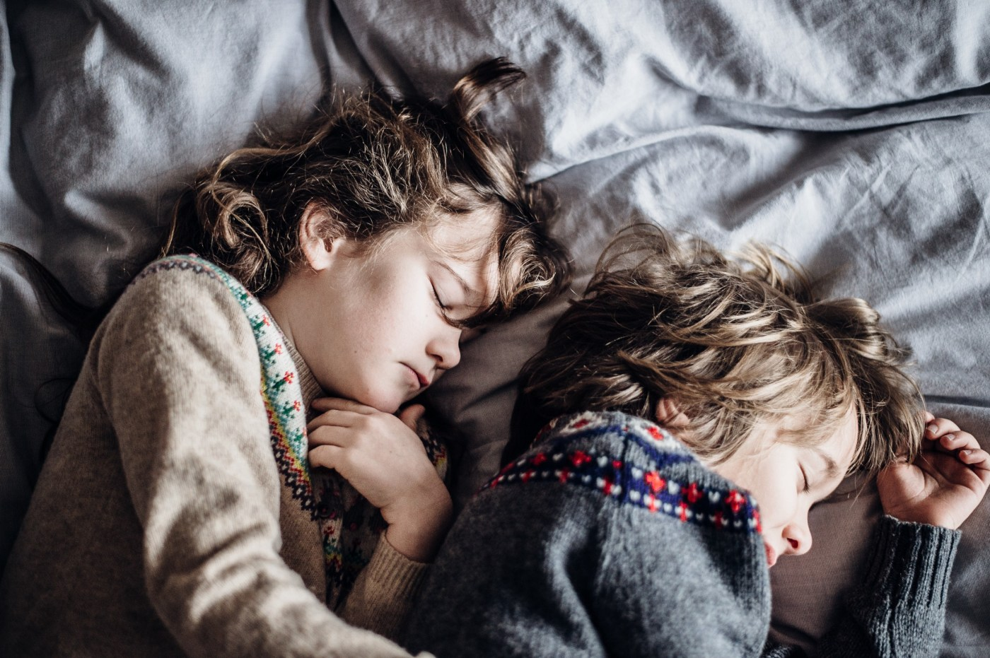 Two children asleep in bed next to each other