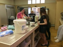 Rosenbaum, Culinary Arts teacher among other duties, showing students the proper technique for mixing the ingredients for doughnuts.