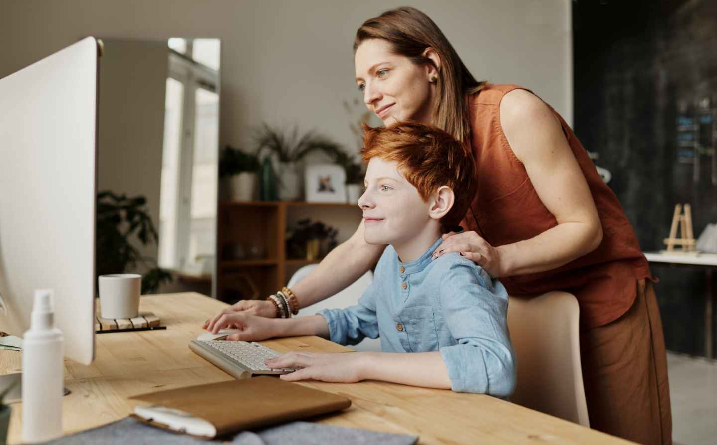 photo of woman teaching his son while smiling
