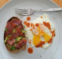 A messy egg, toast, avocado, bacon, chilli sauce #bestlunchever