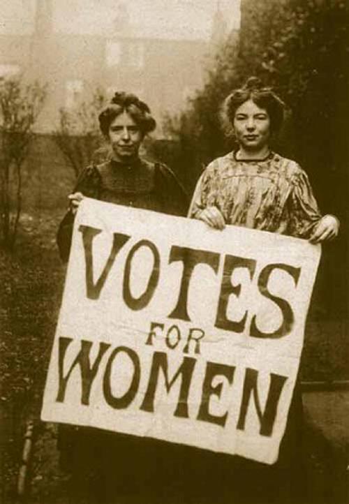 Las sufragistas inglesas Annie Kenney y Christabel Pankhurst portando un cartel reivindicativo del sufragio femenino a principios del siglo XX