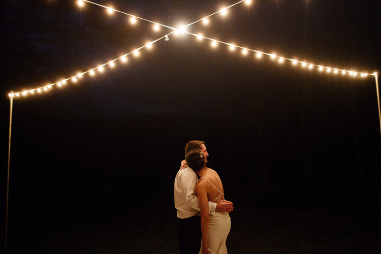 bride and groom dancing under twinkle lights