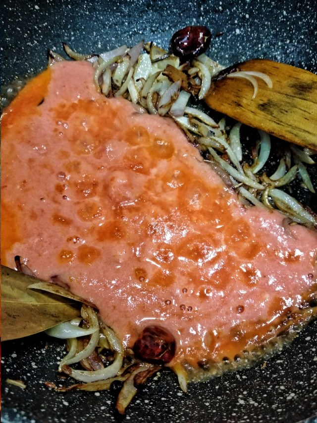 Add the ground tomato - ginger - garlic paste to the caramelized onions