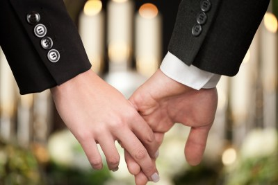 Religion, death and dolor  - couple at funeral holding hands con