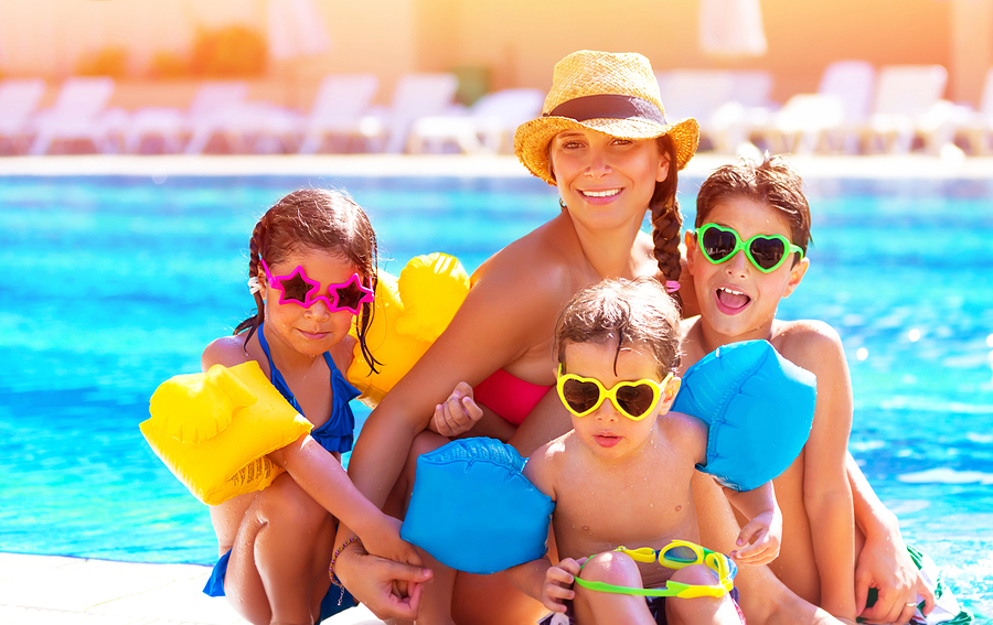 Happy big family having fun at the pool, spending summer vacatio