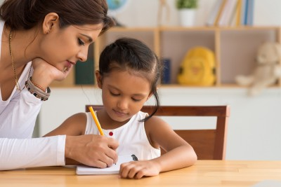 Beautiful Indian woman helping her daughter with homework
