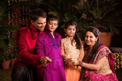 Indian Family in traditional wear playing with sparklers or phuljhadi while
