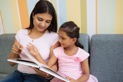 Little girl and her mother sitting on the sofa and reading a book