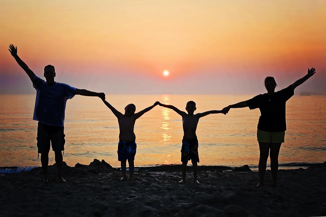 海辺で四人手をつないでいる影