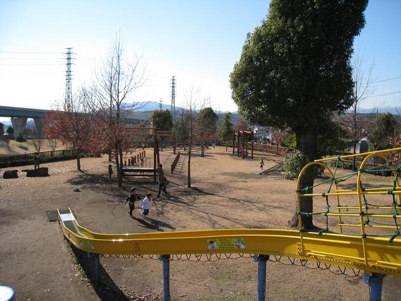 黄色い滑り台と芝生のある公園