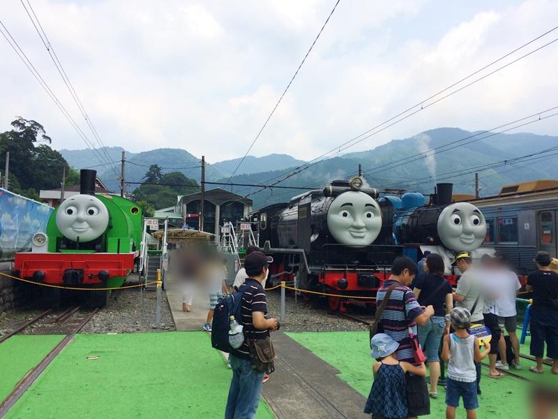 トーマス他2台の顔のついた電車とその前に立つ人々