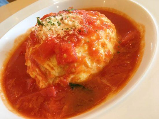 白い皿に乗ったトマトのかかったOMOCHAのオムライス