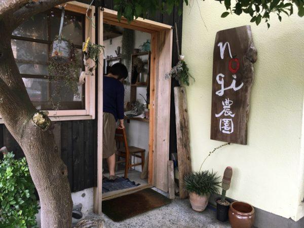 nogi農園と書かれた看板と店内、人が立っている