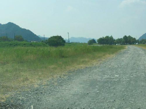 牛妻水辺の楽校まで砂利道が続いている、左に芝生