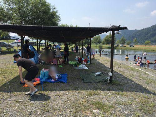 牛妻水辺の楽校の屋根のついた休憩所で涼む人々