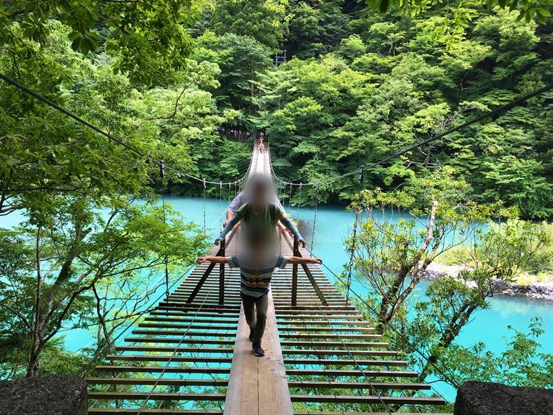 吊り橋を渡る人々、後ろに木々の緑
