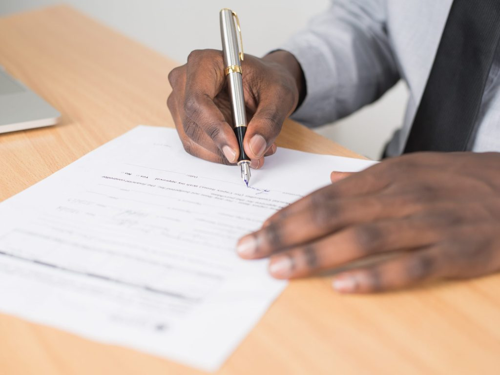 Person holding gray twist pen and white printer paper on brown wooden table. Good Essay Tips.