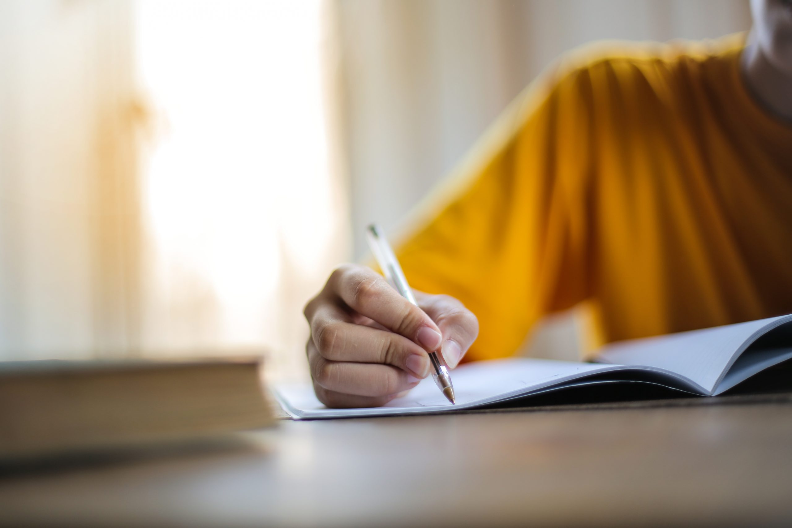 Selective focus photo of person writing