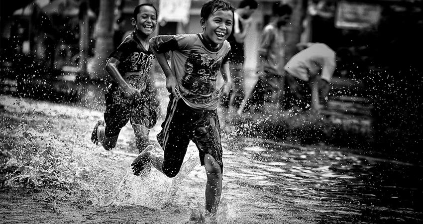 anak bermain sambil hujan hujanan