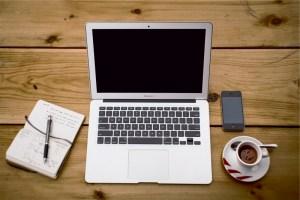 Laptop dan uborampenya, buku, kopi, hape