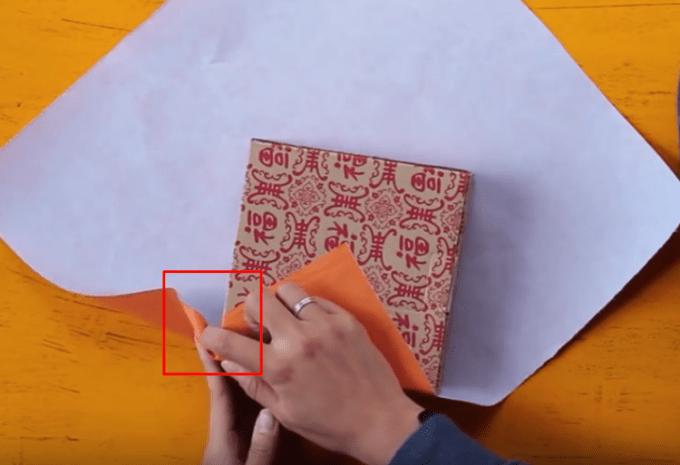 Melipat kertas kado pada sisi bawah